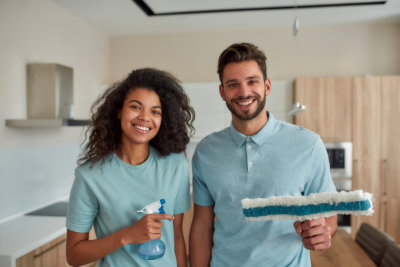 Portrait of happy male and female professional cleaners in uniform holding cleaning supplies