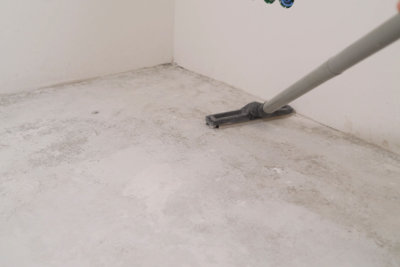 Cleaning cement floor with vacuum cleaner.